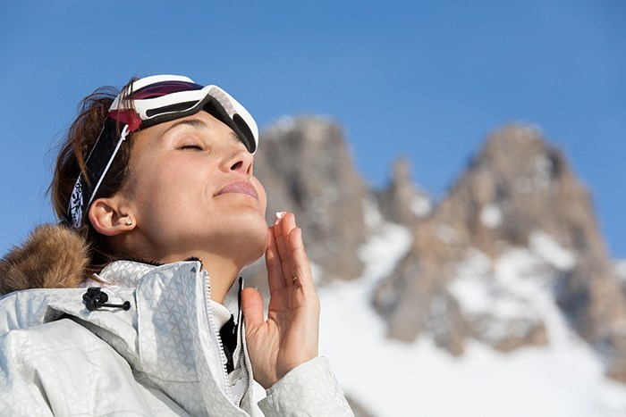 Woman applying an oil-free SPF to her face in winter to prevent skin damage and acne breakouts