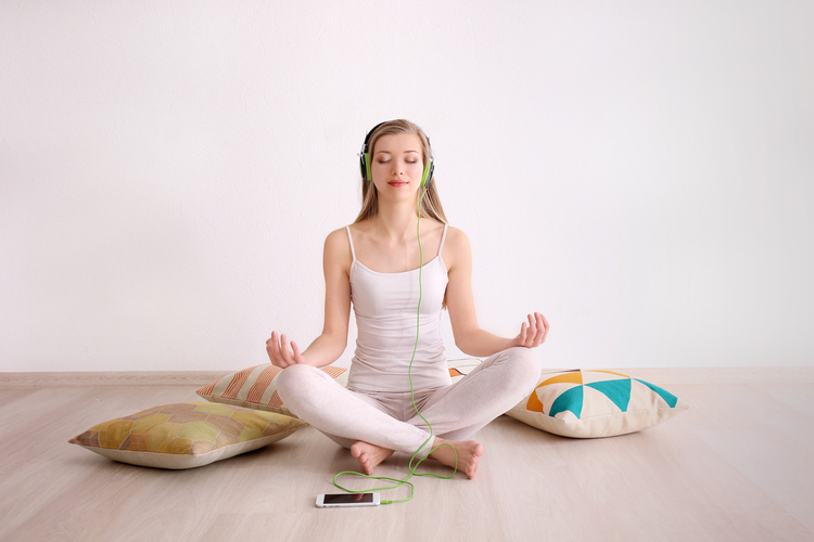 Woman meditating to reduce stress during the holidays and support skin health
