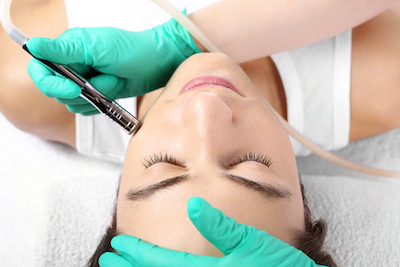 Woman getting a facial to prevent acne breakouts during the holidays