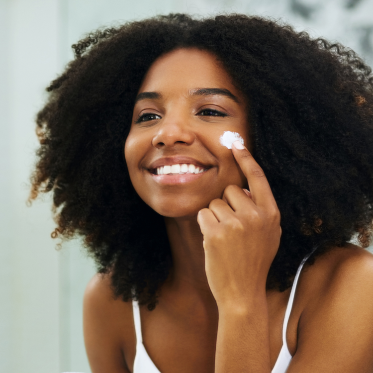 Woman applying MDacne dark spot removal cream for post-acne hyper-pigmentation