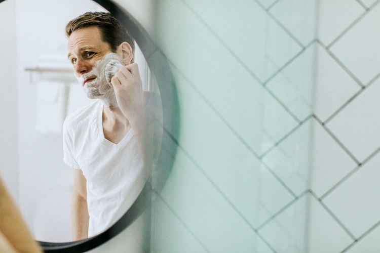 Man letting shaving cream set on face
