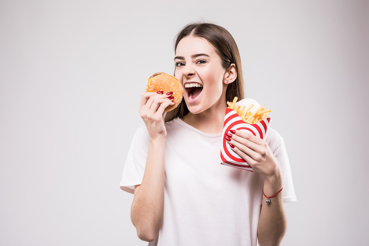 Woman eating fried foods that can cause breakouts on the chin