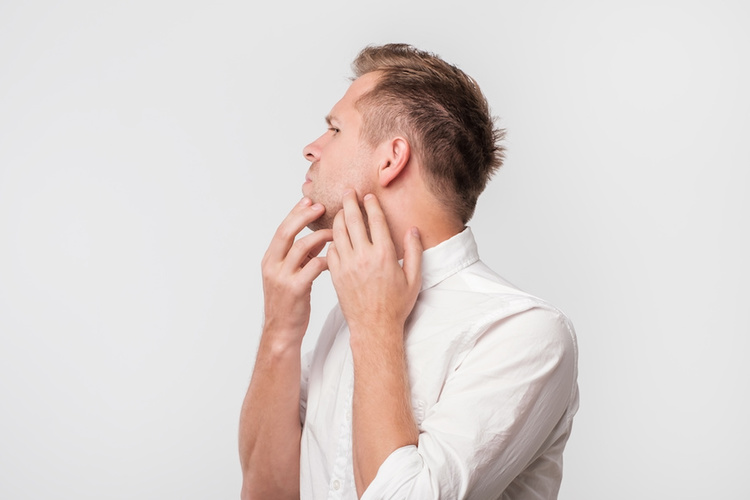 Man touching his face, which can cause more acne breakouts