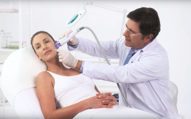 Dermatologist conducting microneedle radio frequency on women with acne scars