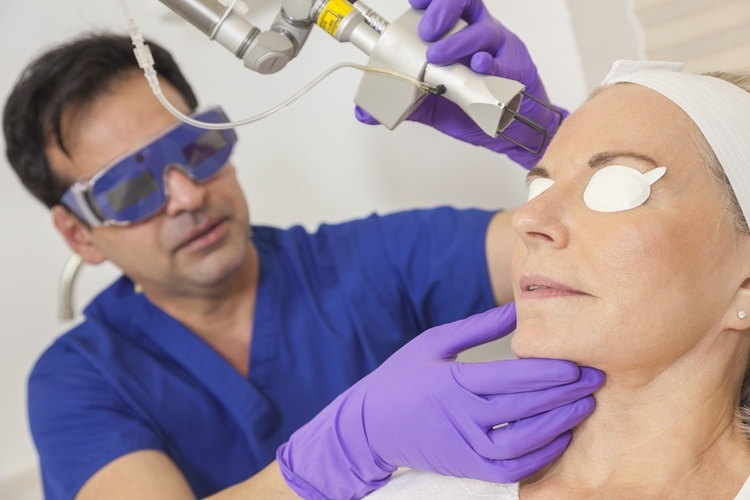 Dermatologist conducting ablative laser resurfacing on woman with acne scars