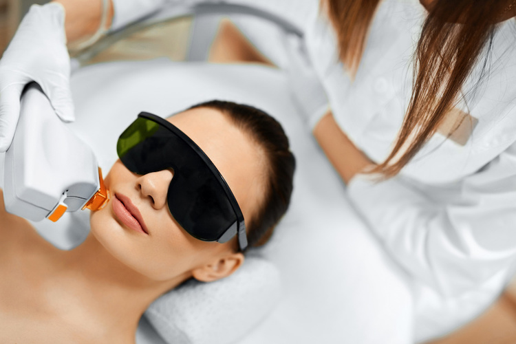 Dermatologist conducting non-ablative laser therapy on woman with acne scars