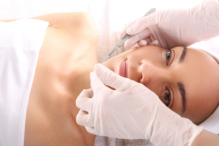 Dermatologist administering submission on woman with depressed acne scars
