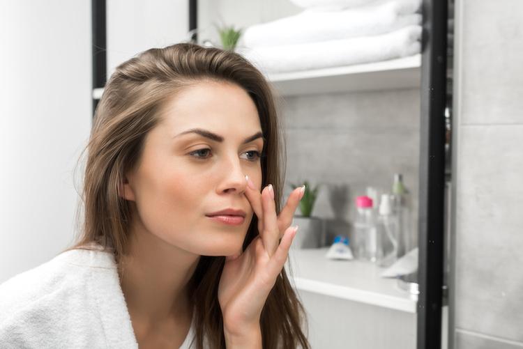 Woman examining skin in mirror to determine skin type