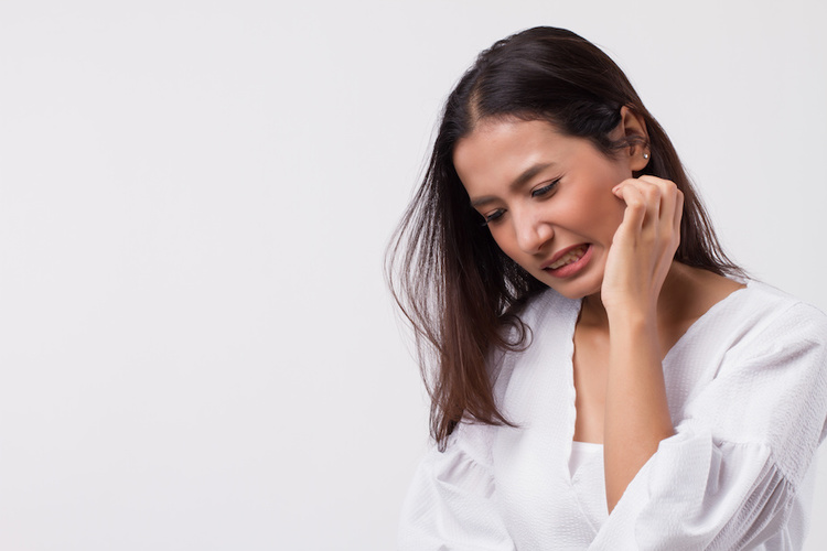 Woman itching sensitive skin that gets easily irritated