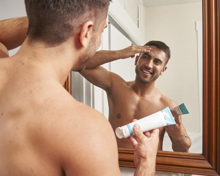 Man applying MDacne Customized Acne Treatment Cream to acne-prone areas of face