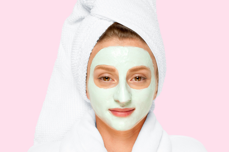 Woman wearing French green clay face mask to treat acne