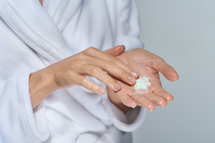 Woman about to apply MDacne oil-free moisturizer