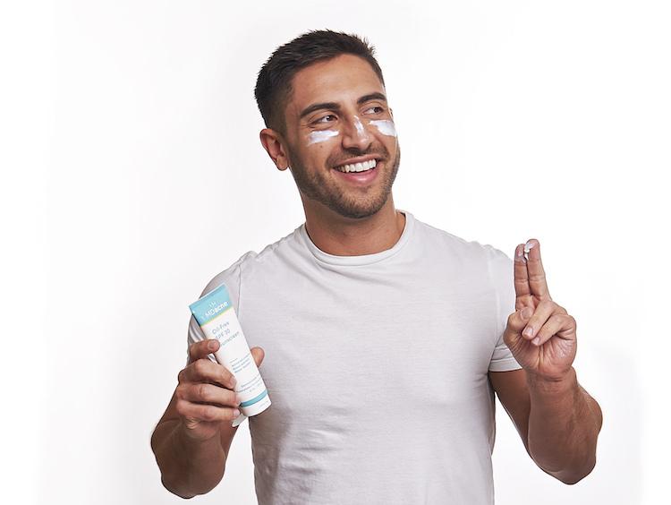 Man applying MDacne oil-free sunscreen as a moisturizer