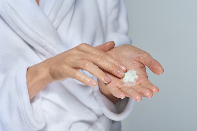 Woman with acne treatment cream in hands