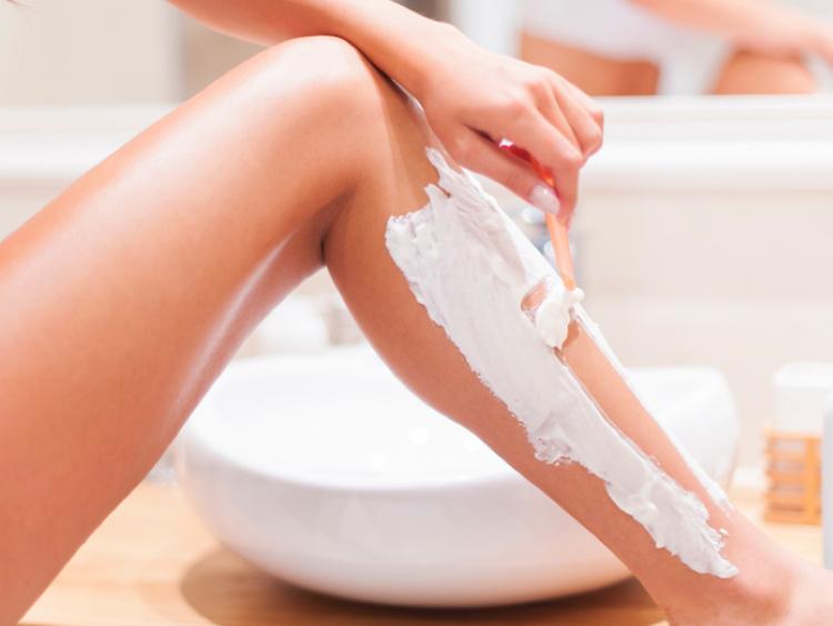 Woman shaving legs with MDacne Soothing Shave Cream