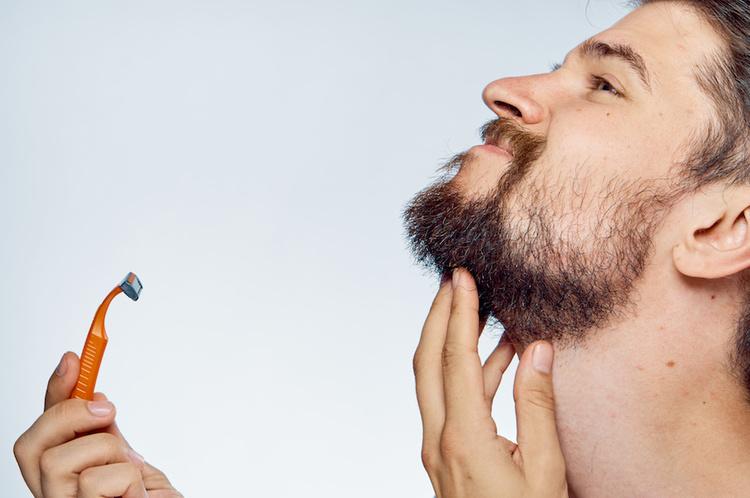 Man holidng shaving razor to face
