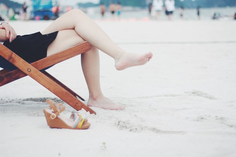 Woman on beach with smooth shaved legs without razor bumps